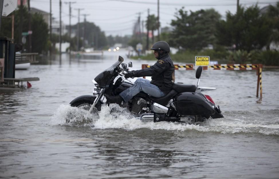 A motorcyclist navigates through flood waters in Garden City Beach