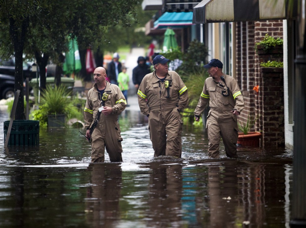 Beauregard, Attender and Rogers of the Georgetown Fire Department, wade through flooded Front Street in Georgetown, South Carolina