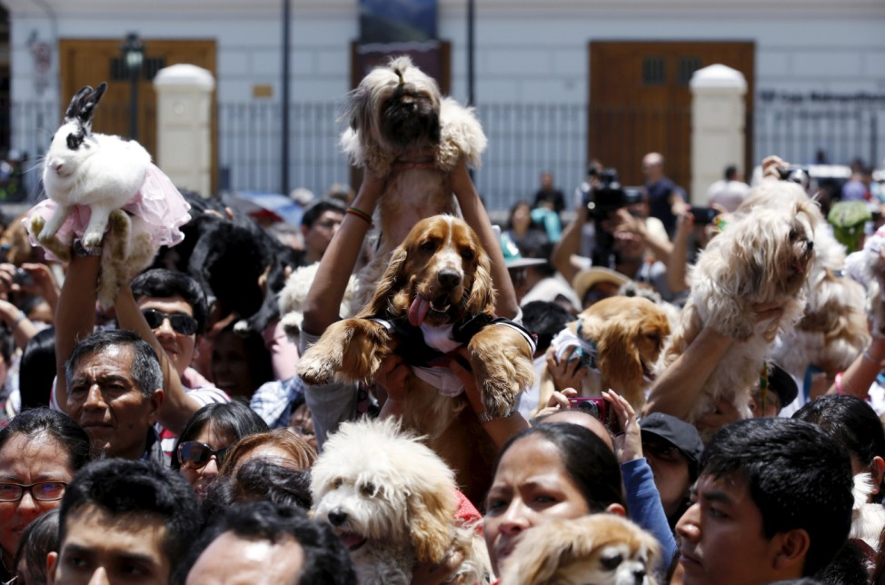 Owners holding their pets attend a religious and blessing ceremony outside the San Francisco church in Lima