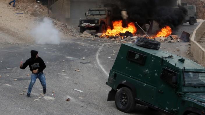 Palästinenser-Präsident: Die Enttäuschung befeuert die Gewalt: Ein Palästinenser wirft eine Flasche auf ein israelisches Militärfahrzeug in Nablus Westjordanland.