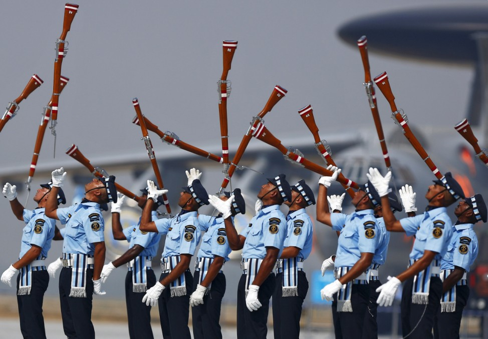 Indian Air Force soldiers toss their rifles as they perform during the full-dress rehearsal for Indian Air Force Day at the Hindon
