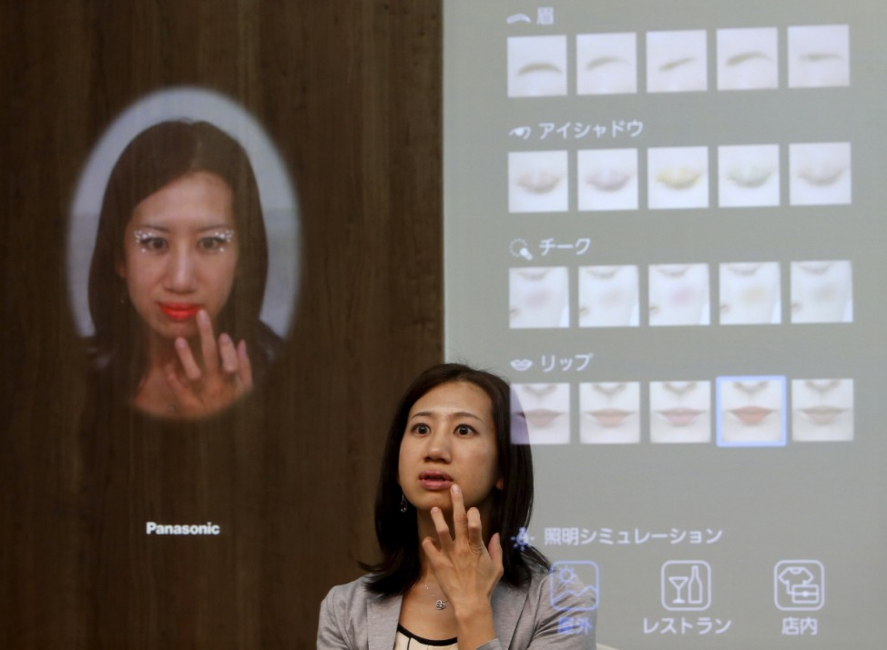 A woman is reflected in Panasonic Corp's interactive mirror during a demonstration at CEATEC  JAPAN 2015 in Makuhari