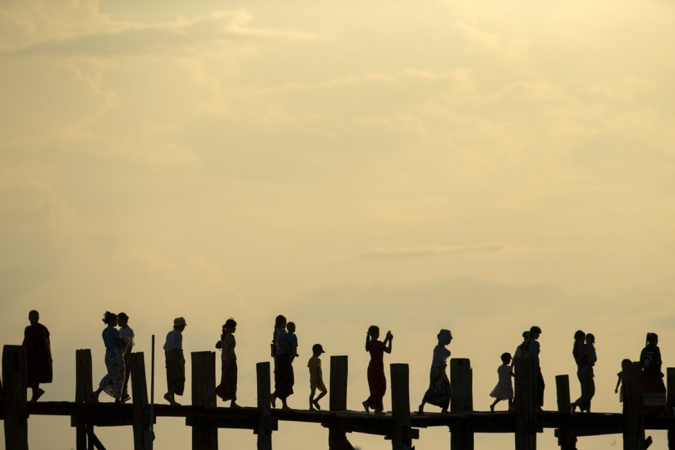 People cross U Bein bridge over Tuangthaman Lake in Mandalay, Myanmar