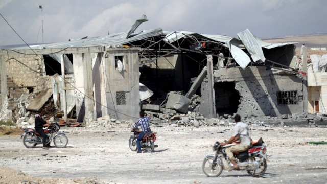Men on motorcycles a site hit by what activists said were airstrikes carried out by the Russian air force in the town of Babila, in the southern countryside of Idlib, Syria,