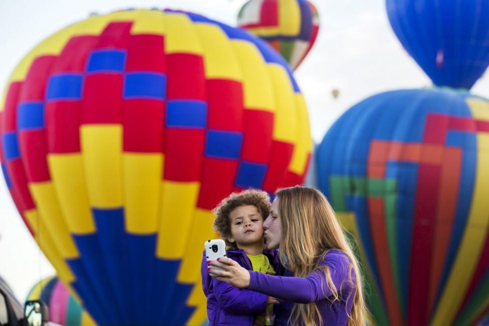 A woman and child take a photograph as hot air balloons lift off during the 2015 Albuquerque International Balloon Fiesta in Albuquerque, New Mexico