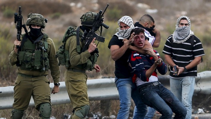 Undercover Israeli security personnel and Israeli soldiers  detain a wounded Palestinian protester during clashes near the Jewish settlement of Bet El