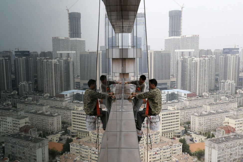 Labourers clean the glass windows outside a 30-floor business building in Qingdao