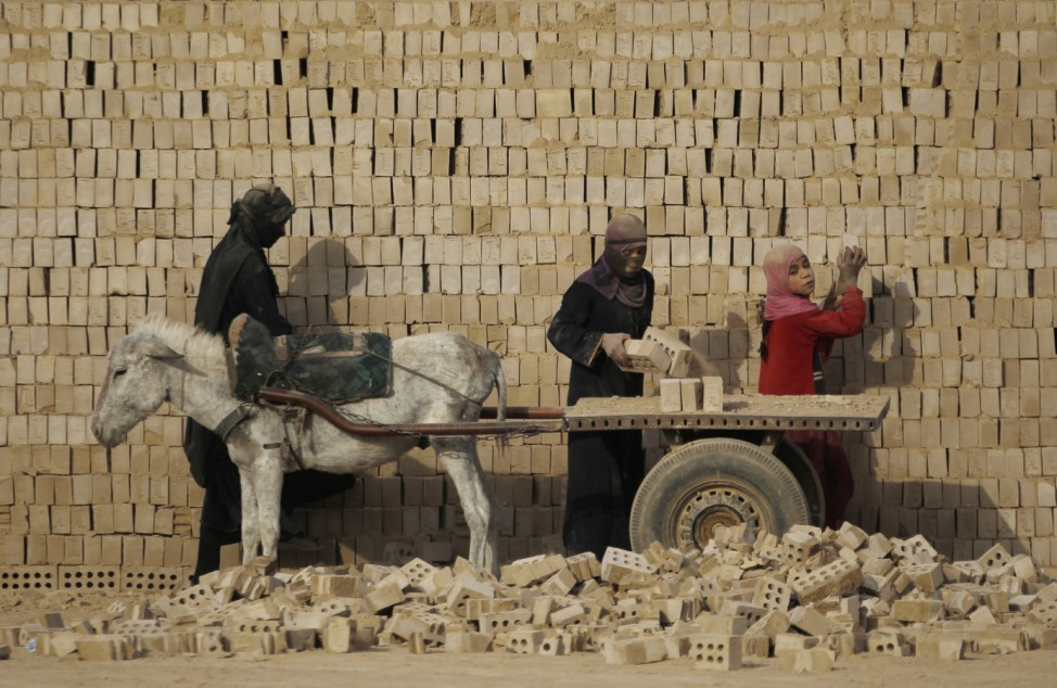 Female workers load bricks on a donkey driven cart in a brick factory in the town of Nahrawan east of Baghdad