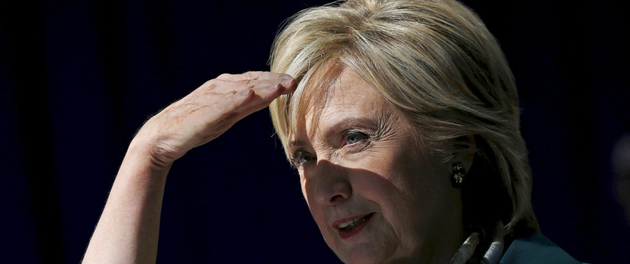 U.S. Democratic presidential candidate Hillary Clinton shields her eyes from the sun at a campaign event in Davenport