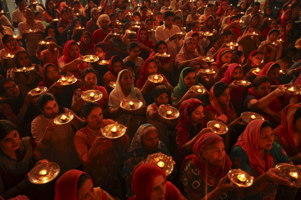 Hindu devotees with earthen oil lamps pray inside a temple during the Navratri festival in Chandigarh