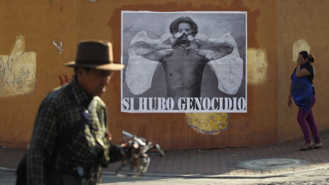 A vendor and a woman walk past a poster on the streets of Guatemala City