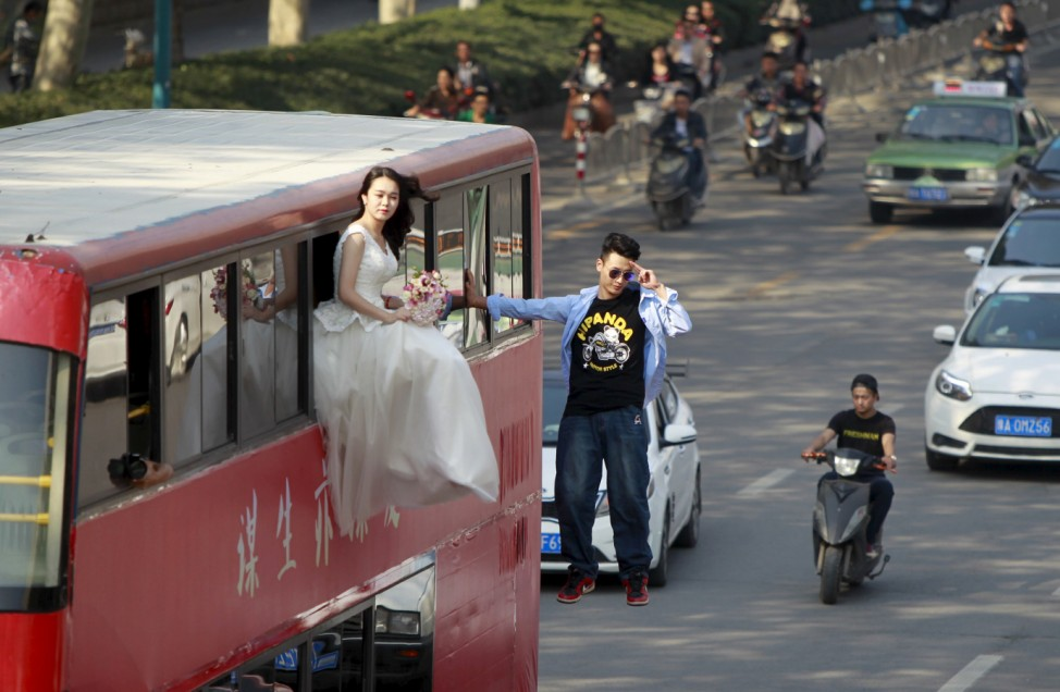 Magician Lei Xin is seen suspended outside a double-deck bus, next to a woman in a wedding gown, as they participate in a performance on a street in Zhengzhou