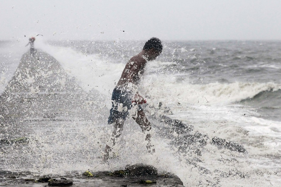 A boy searches for reusable plastic bottles while being pelted by waves brought by typhoon Koppu in Manila Bay
