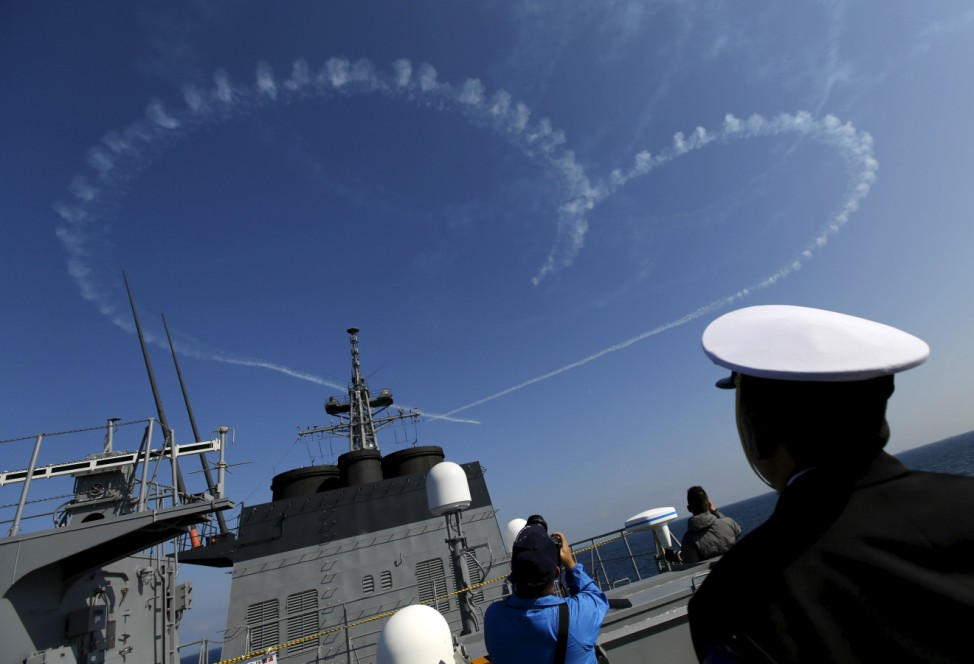 Member of JMSDF looks at a performance by JASDF aerobatic flight team 'Blue Impulse' during JMSDF's fleet review at Sagami Bay, off Yokosuka