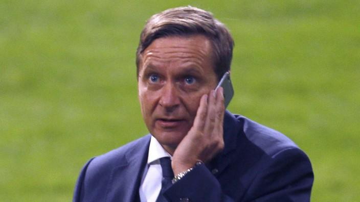 Schalke 04's manager Heldt listens at his mobile phone after the Bundesliga first division soccer match against Hertha Berlin in Gelsenkirchen
