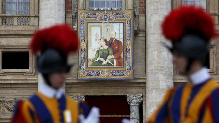 A tapestry showing Louis and Zelie Martin, parents of St. Therese of Lisieux, hangs from a balcony as Pope Francis leads the mass for their canonization in Saint Peter's Square at the Vatican