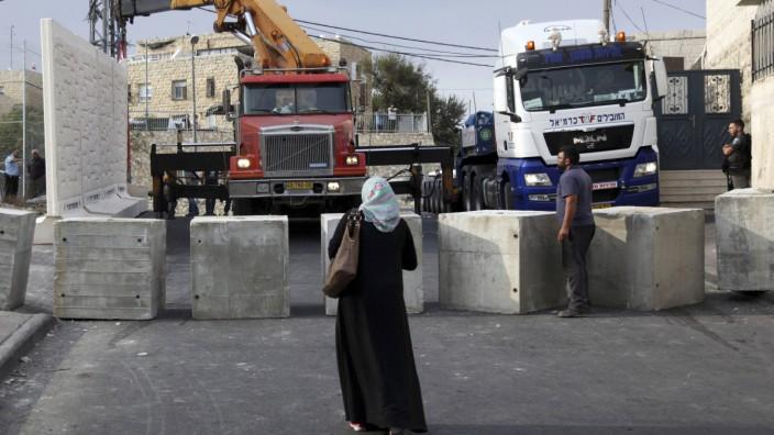 Israel: Israel ließ mitten in Jerusalem entlang der Grenze zwischen einem palästinensischen und einem jüdischen Viertel ein Stück Mauer errichten - und stoppte das Vorhaben schnell wieder.