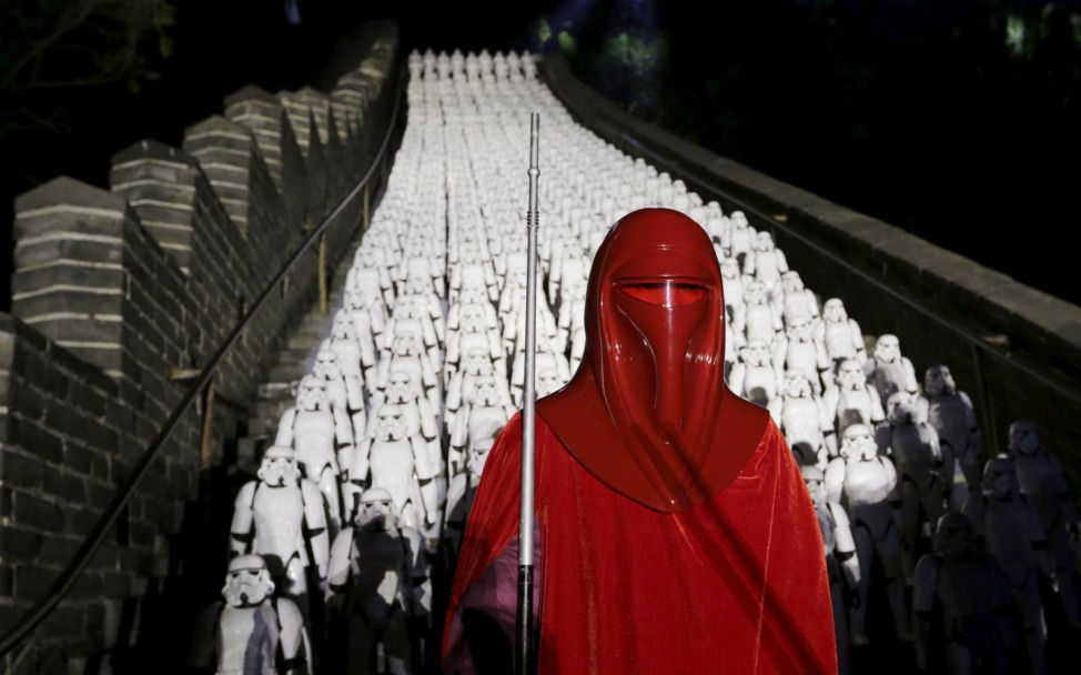 A fan dressed as an Imperial Royal Guard character from 'Star Wars' poses for a photo in front of five hundred replicas of Stormtroopers during a promotional event for 'Star Wars: The Force Awakens' at the Great Wall of China