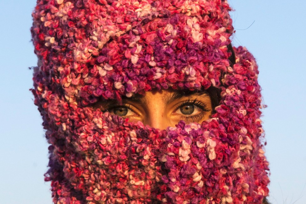 A woman from Syria looks on as she waits to cross the border with Croatia near the village of Berkasovo