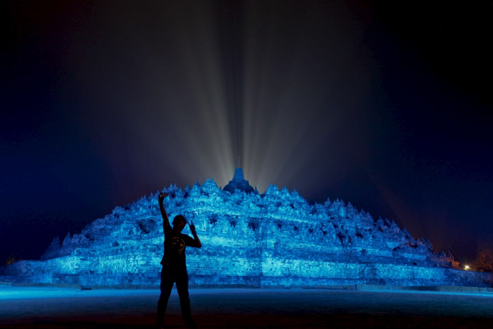 A visitor takes a picture as the 9th century Borobudur temple is illuminated with blue light to honour the 70th anniversary of the United Nations in Magelang, Central Java