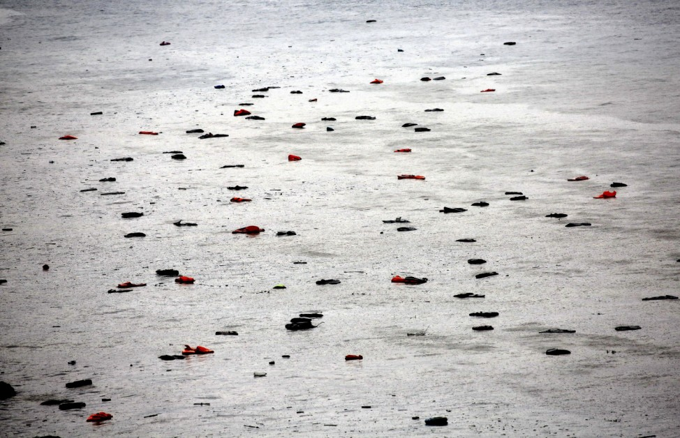 Life vests and tubes left by migrants float by a beach during a rain storm on the Greek island of Lesbos