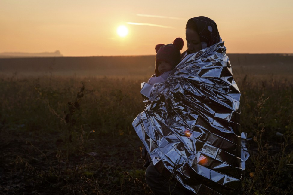 A migrant woman wrapped in a thermal blanket carries a child as she walks through a field to cross the border with Croatia near the village of Berkasovo