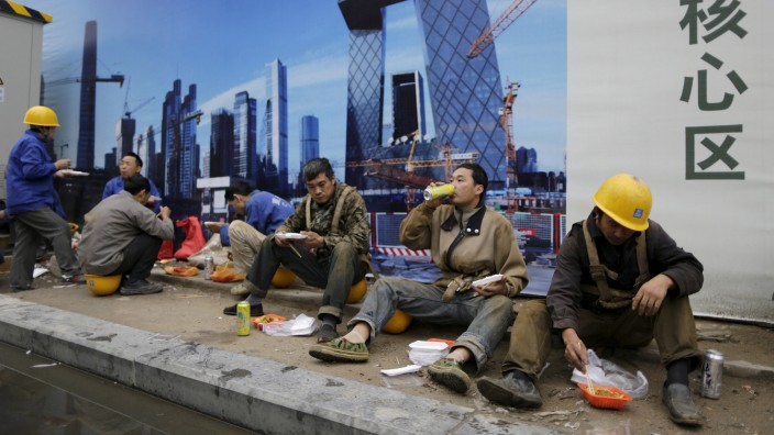 Construction workers have lunch as they sit in front of a poster bearing a picture of the Central Business District (CBD) area, outside a construction site in Beijing