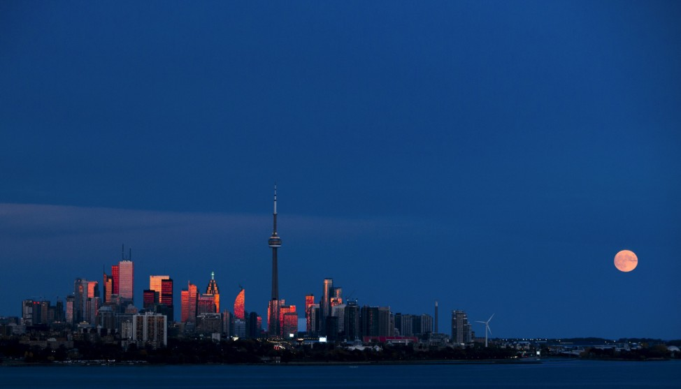 The moon rises behind the skyline in Toronto