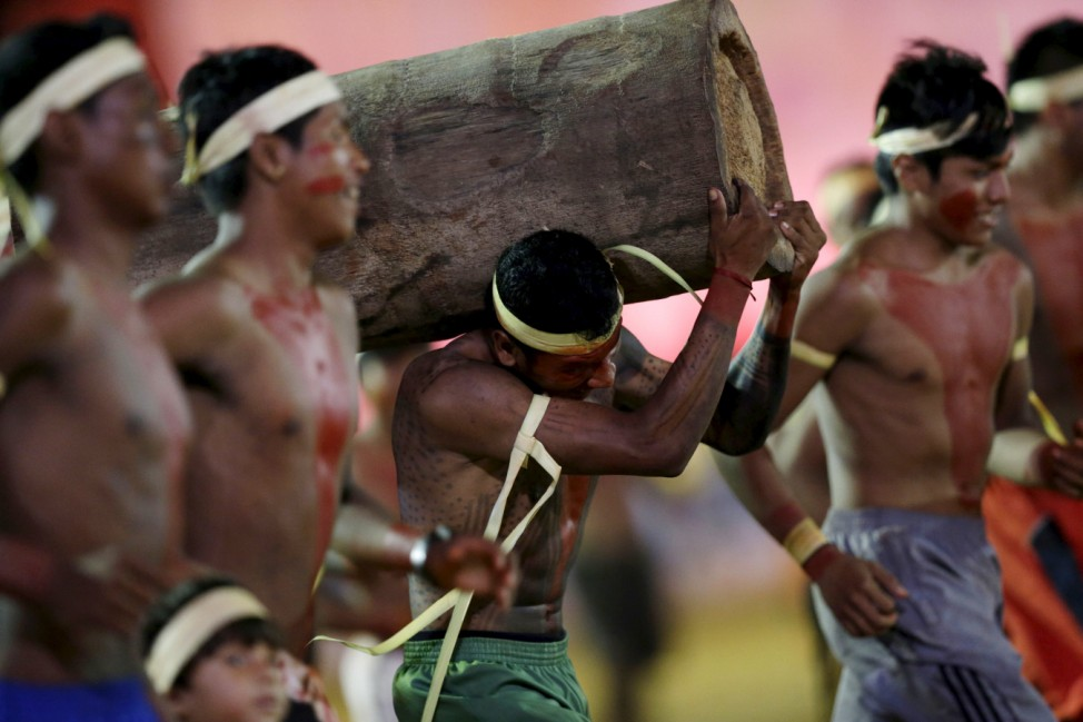 An indigenous man from the Xerente tribe competes in a relay race carrying a tree trunk during the first World Games for Indigenous Peoples in Palmas