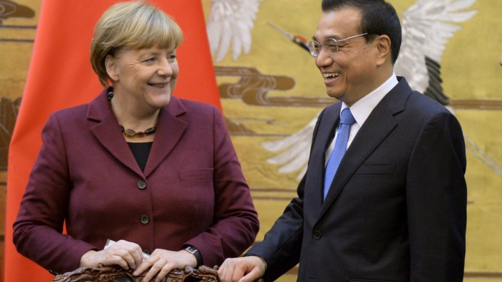 German Chancellor Angela Merkel and Chinese Premier Li Keqiang smile after a signing ceremony at the Great Hall of the People in Beijing