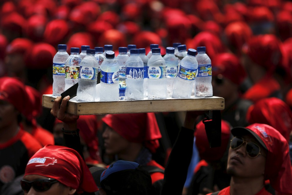 A street vendor holds a tray of bottled water as Indonesian union workers march toward the presidential palace during a protest against their minimum wages in Jakarta