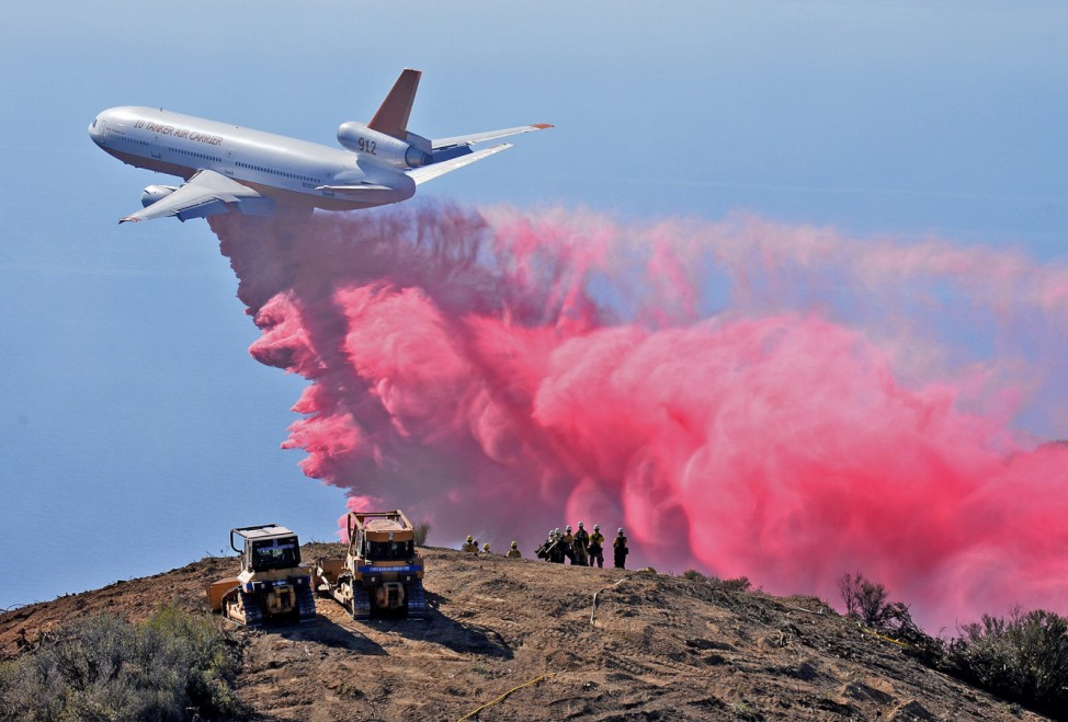 A DC-10 air tanker drops phos-check on the Gibraltar Fire as firefighters watch from a peak in the Los Padres National Forest above Santa Barbara, California in this handout photo