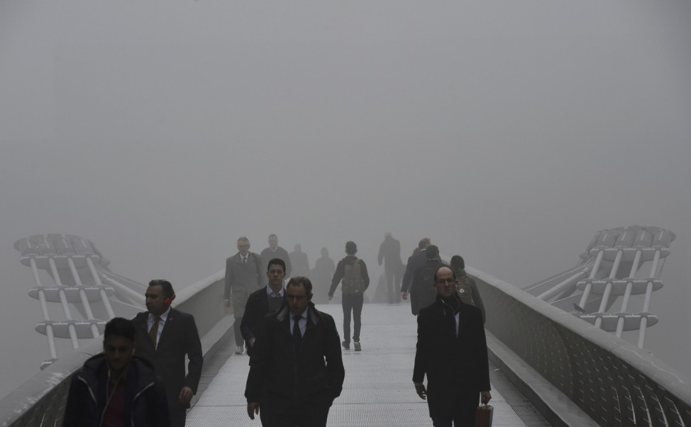 City workers cross the Millennium footbridge over the River Thames on a misty morning in London, Britain