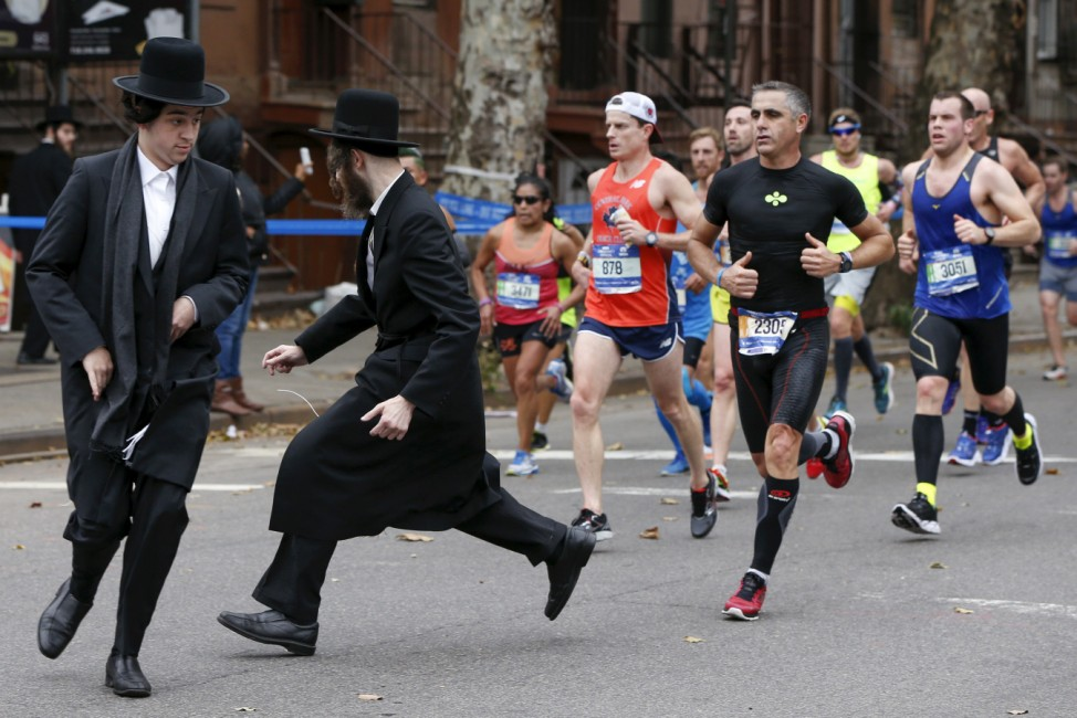 Orthodox Jewish men try to cross Bedford Avenue in the Williamsburg section of the Brooklyn borough during the 2015 New York City Marathon in New York