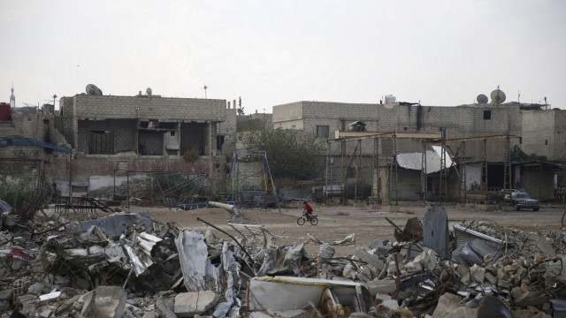 A resident rides a bicycle near damaged buildings in the town of Douma, eastern Ghouta in Damascus, Syria