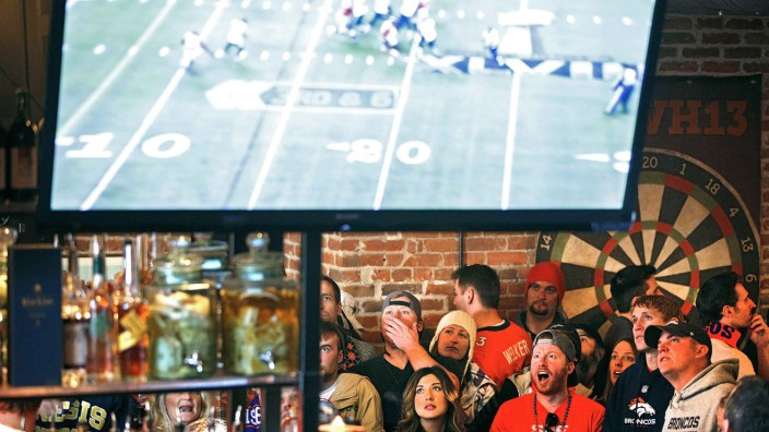 Broncos fans react to a play while watching their team's NFL Super Bowl XLVIII football game against the Seahawks at a bar in Denver