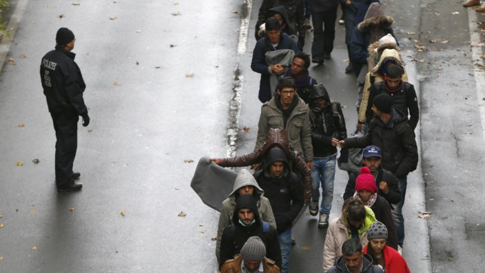 Migrants walk along street after passing Austrian-German border in Achleiten