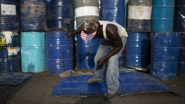 A man beats a sheet of metal cut from an oil barrel to use as recycling material in Kamukunji, Nairobi