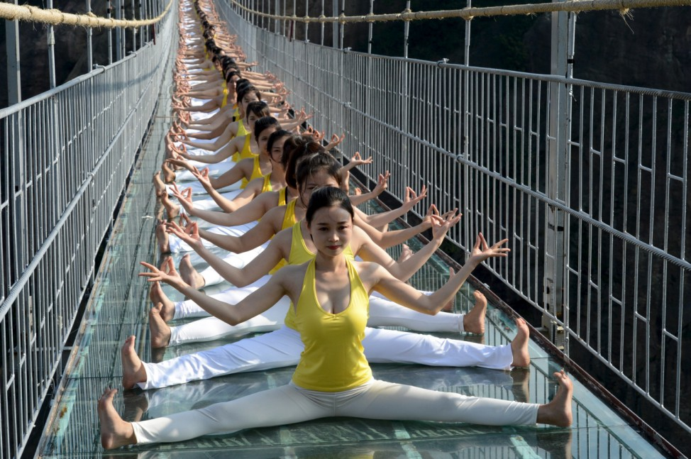 Women practice yoga during a performance on a glass bridge at the Shiniuzhai National Geo-park in Pingjiang county