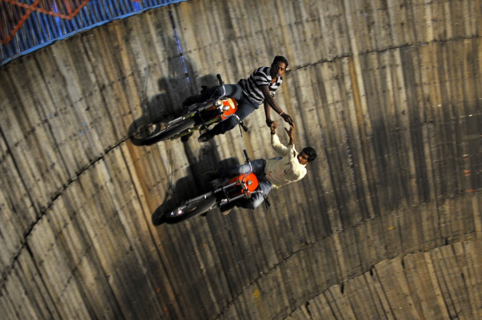 Stunt performers ride their motorcycles on the walls of Well of Death at a fair on the outskirts of Bengaluru