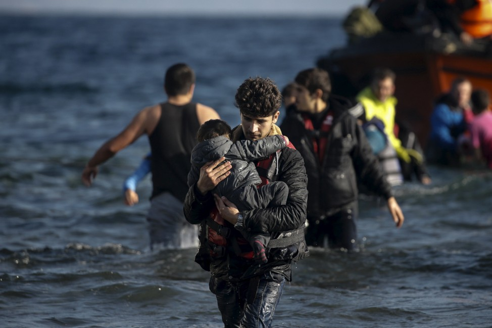 A young man carries a child as refugees and migrants arrive on a boat on the Greek island of Lesbos