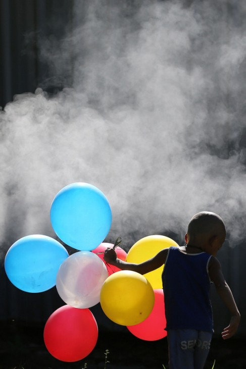 A Filipino boy plays with balloons beside a burning trash in Manila, Philippines