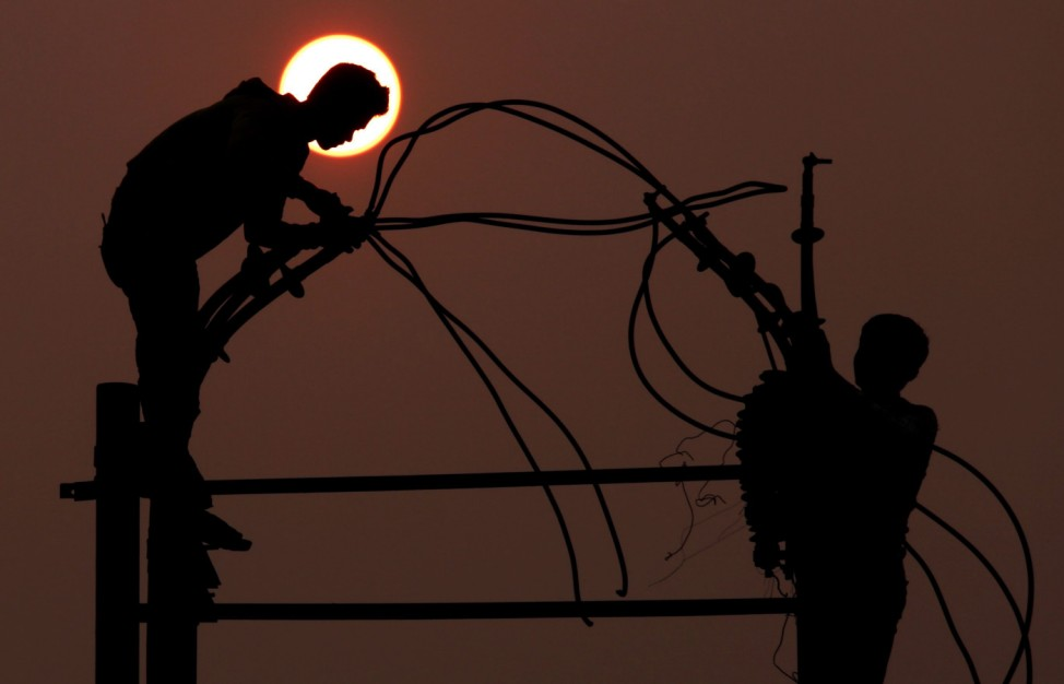 Workers fix an electric pole in Amritsar