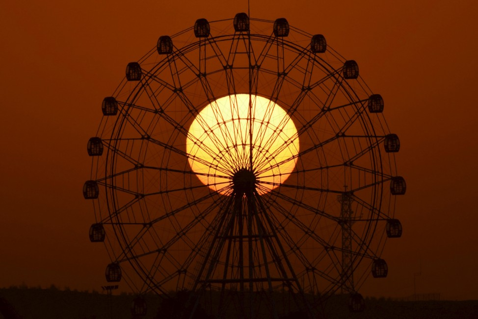 The sun is seen rising behind a skywheel in Korla
