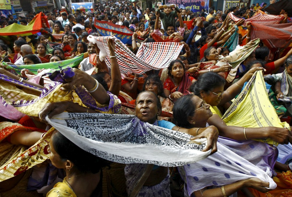 Hindu devotees hold up scarves to receive rice as offerings being distributed by the temple authority on the occasion of the Annakut festival in Kolkata