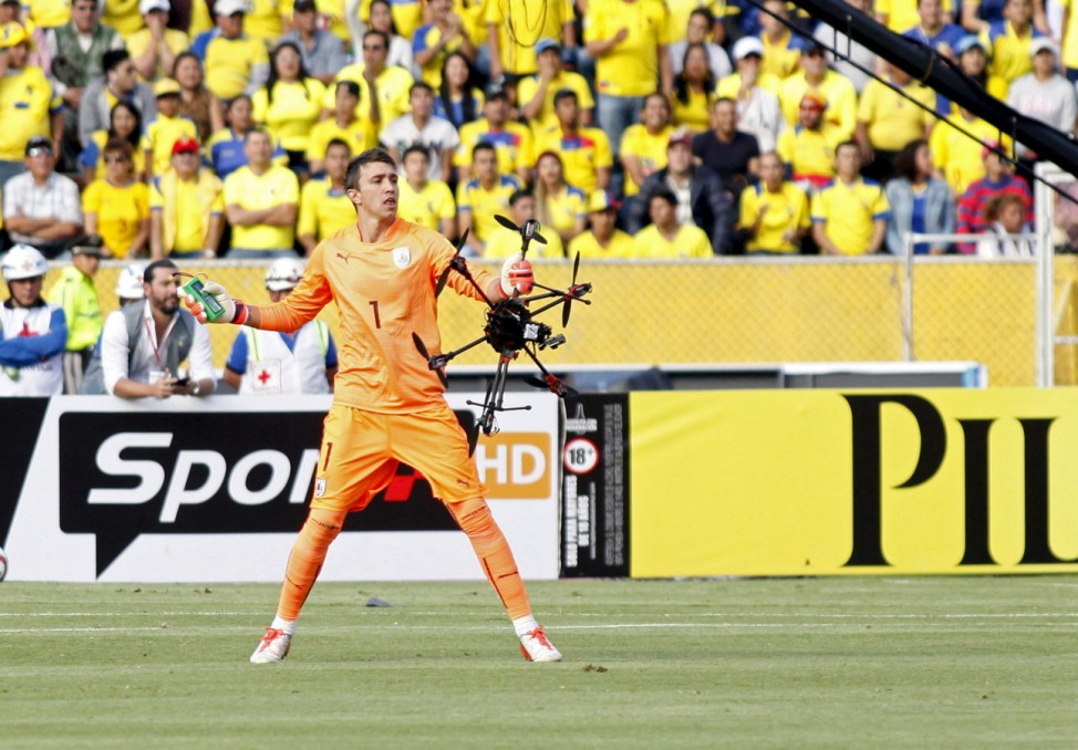 Uruguay goalkeeper Fernando Muslera holds a drone which fell on the field during their 2018 World Cup qualifying soccer match against Ecuador at Atahualpa stadium in Quito