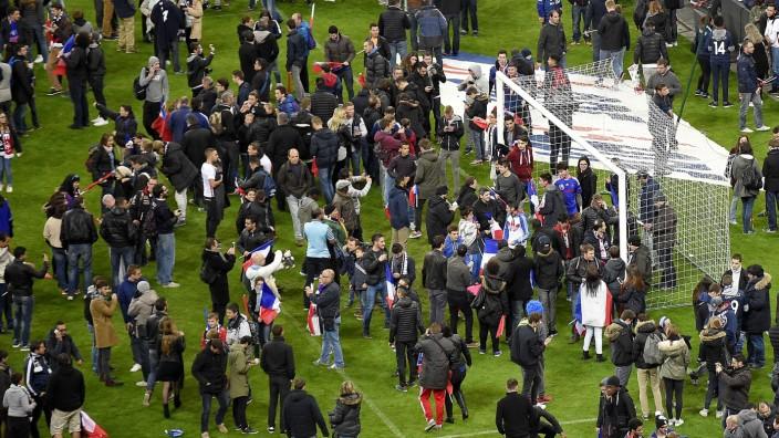 Zuschauer des Spiels Frankreich - Deutschland auf dem Spielfeld des Stade de France.