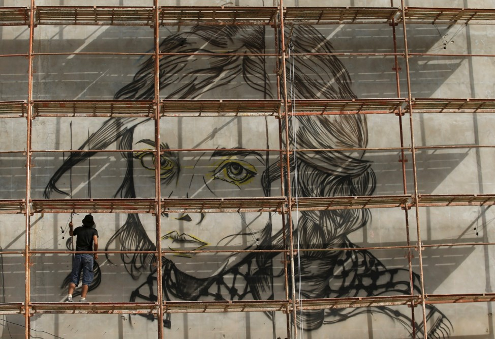 Palestinian artist Belal Khaled paints a mural depicting a Palestinian child on a tower wall in Gaza City