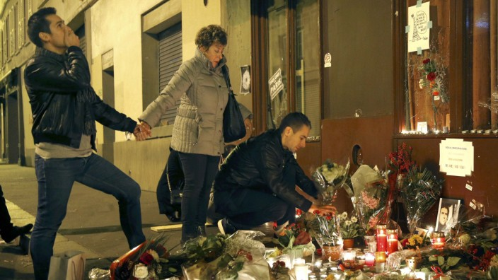 People gather outside Le Carillon restaurant, one of the attack sites in Paris