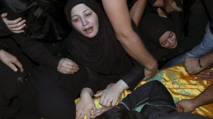 Relatives mourn over the coffin of Hezbollah member, Adel Akram Termos, who was killed in the two explosions that occurred on Thursday in Beirut's southern suburbs, during his funeral in Tallousa village, southern Lebanon